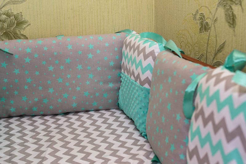 toddler bed with colorful baby bumpers for protection