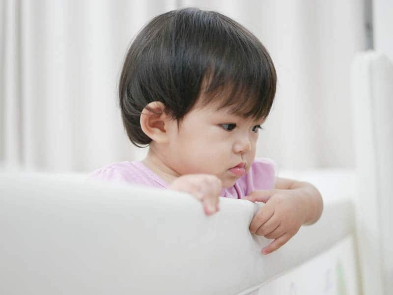 toddler standing in the bed and holding on a bed rail