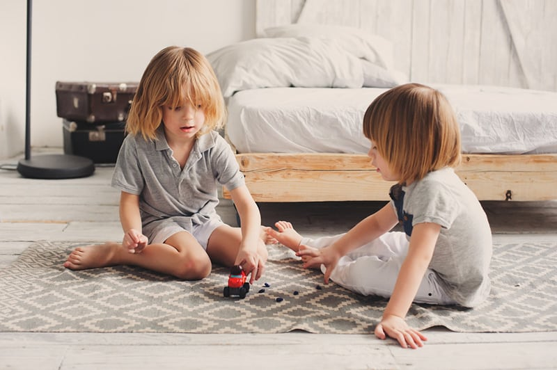 two happy siblings playing with toy cars at home in the morning