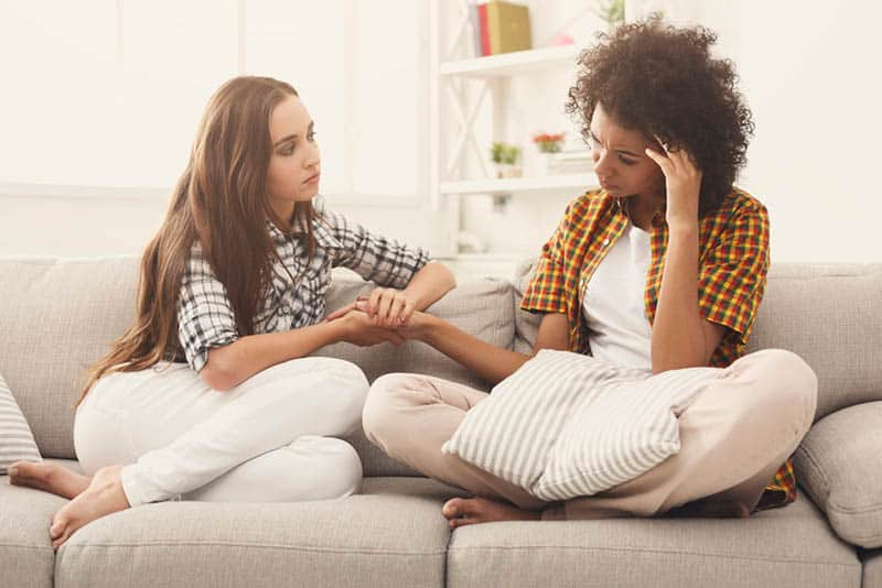 woman comforting her sad friend on the couch
