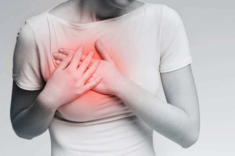 woman feeling breast pain and touching her chest with hands