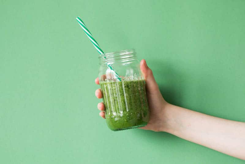 woman holding fresh smoothie made from greens