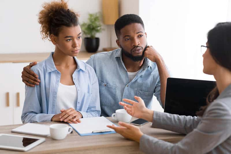 worried couple talking with money counselor in the office