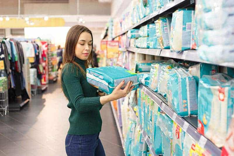 young mother in store buying pampers diapers