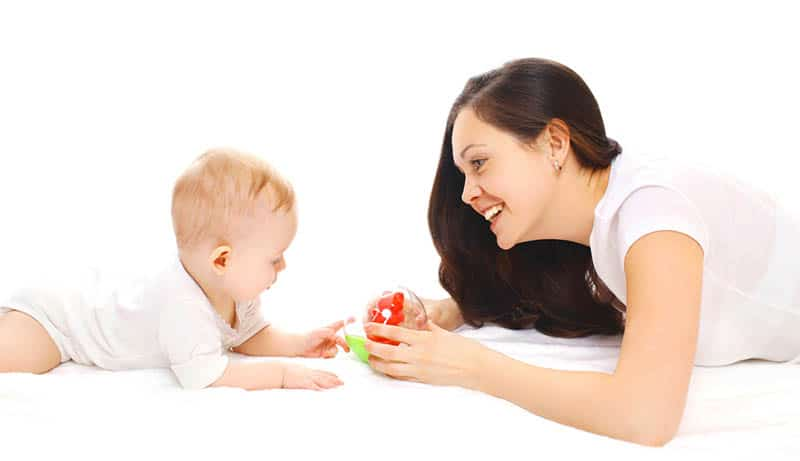 young mother playing with baby on the floor