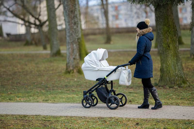 young mother pushing white baby stroller through the park