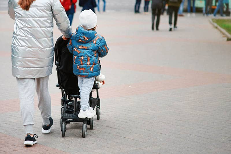 young mother walking with her son driving on a stroller