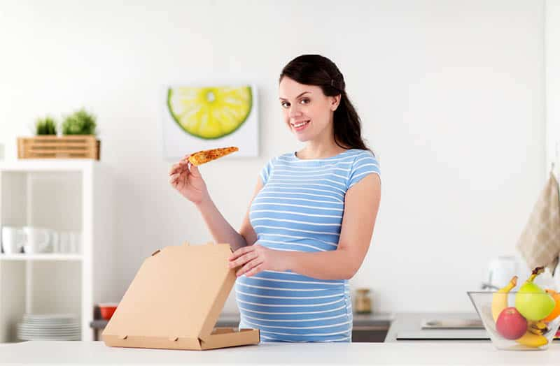 young pregnant woman eating a slice of pizza in the kitchen