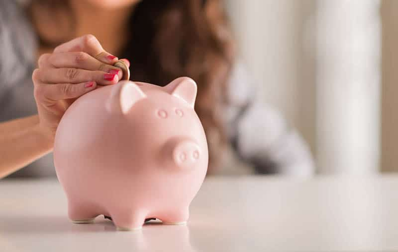 young woman putting coin in pink piggy bank