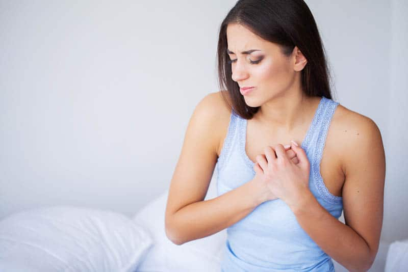young woman sitting on the bed and feeling pain in breasts