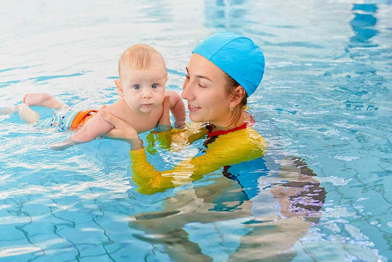 young woman teaching baby to swimm in the pool
