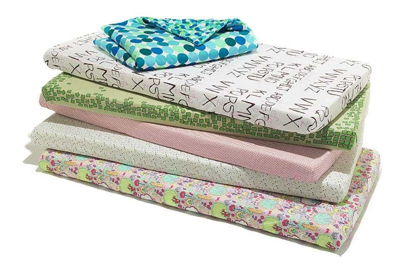 a few baby crib sheets in different colors and designs