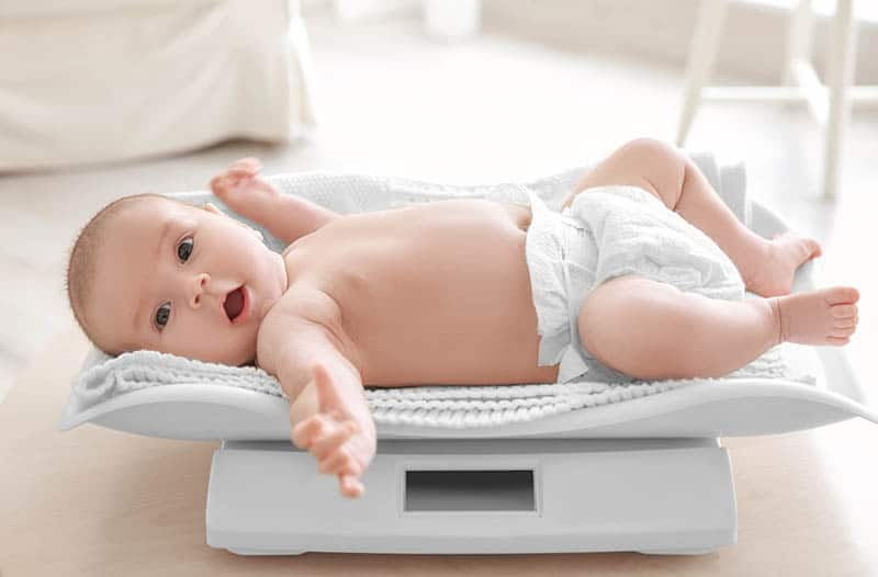 adorable baby boy wearing diaper and lying on the scale at home