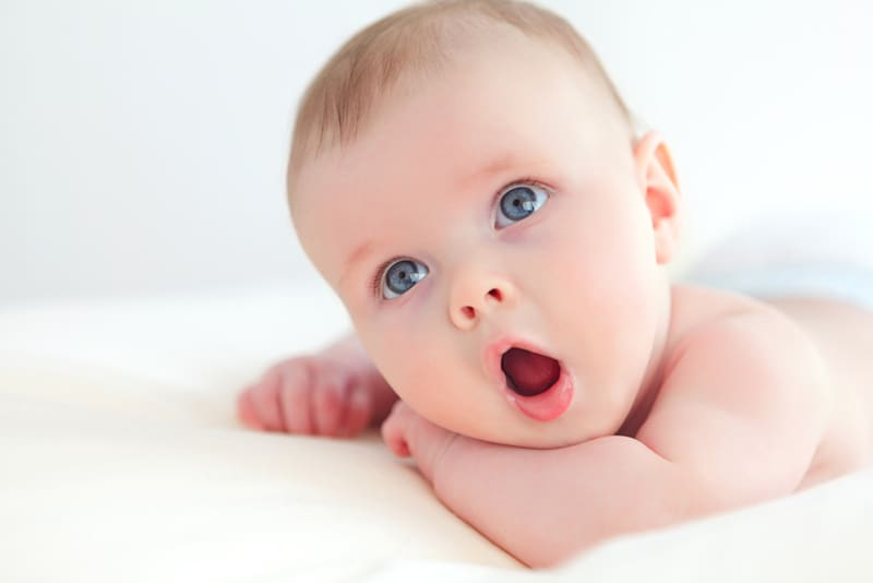 adorable baby lying on tummy and holding mouth open