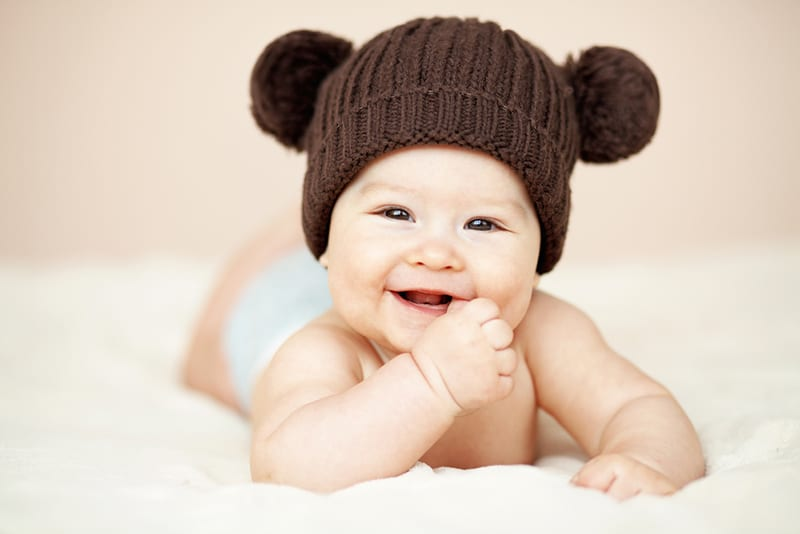 adorable baby wearing a teddy hat and smiling while lying on tummy