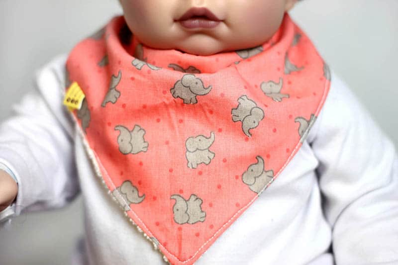 adorable baby with chunky cheeks wearing an orange bib with elefant images on it