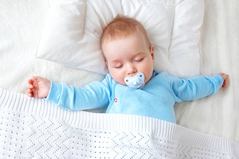 adorable baby with pacifier sleeping on bed covered with blanket