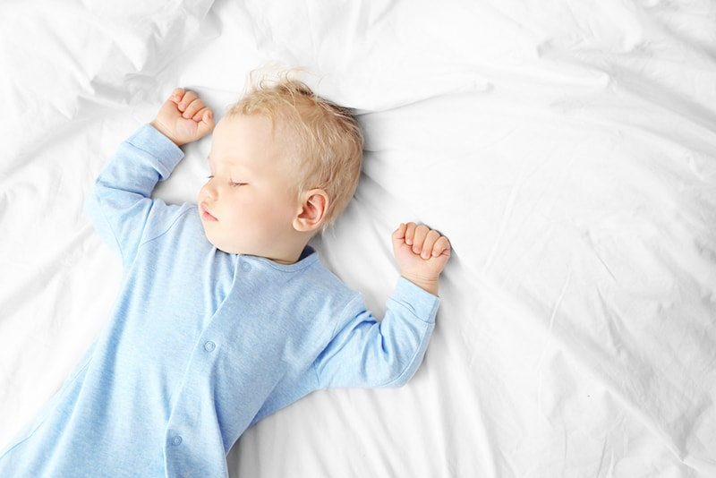 baby boy with blue hair sleeping on white sheets with hands up