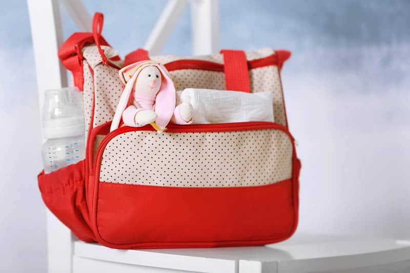 baby diaper bag for moms with baby items on the white chair