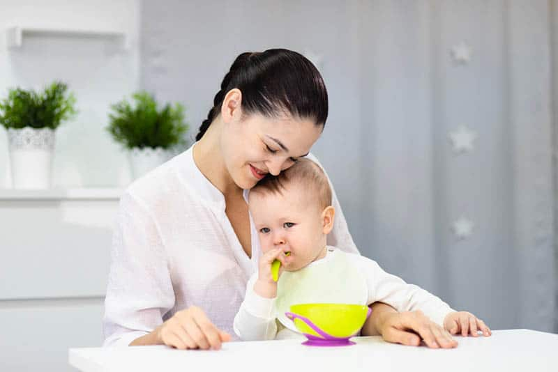 baby eating food with spoon while sitting in lap of happy mother