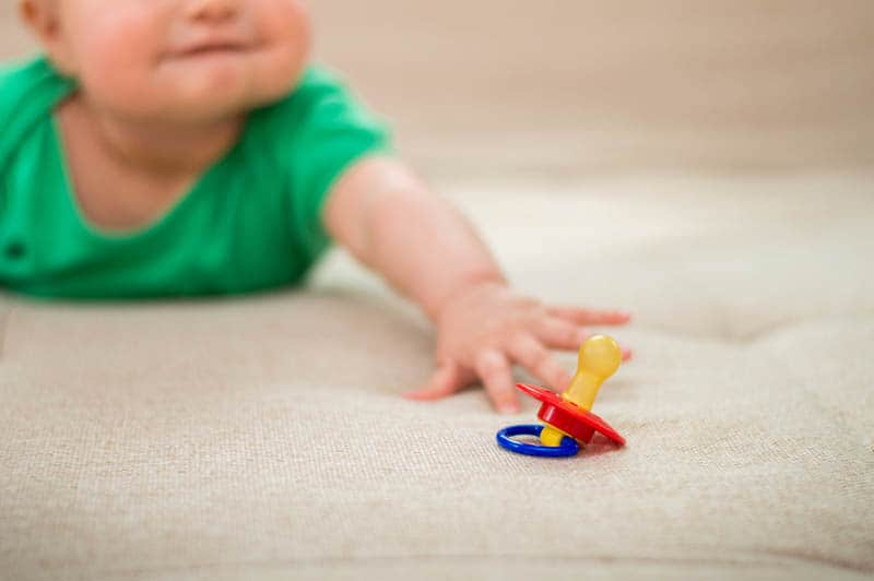 baby lying on belly and trying to reach a colorful pacifier on the floor
