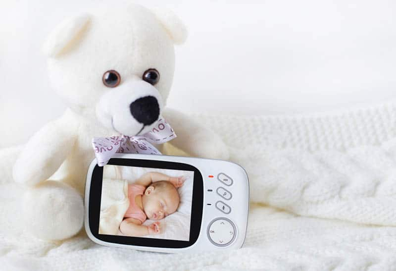 baby monitor for security of the baby surrounded by a teddy bear