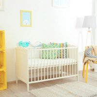 a crib and yellow furniture in the nursery