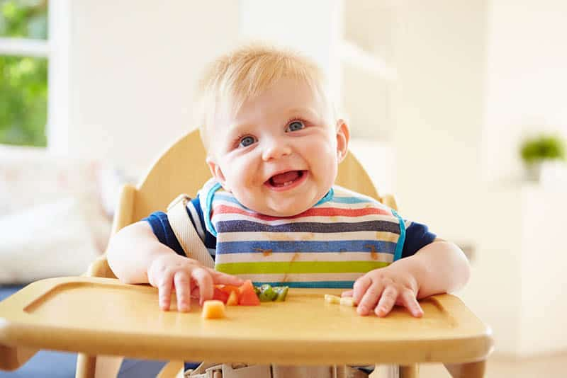 baby with colorful bib eating food in high chair