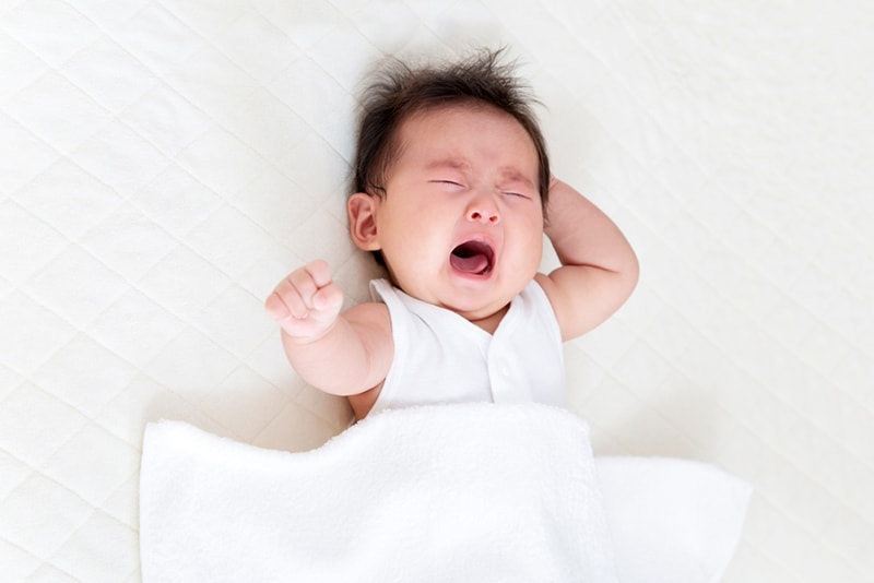 baby with long hair crying while lying on bed covered with white sheet