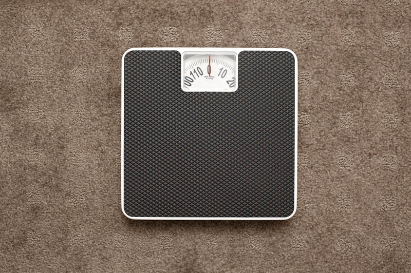 bathroom scale on the brown floor indoors