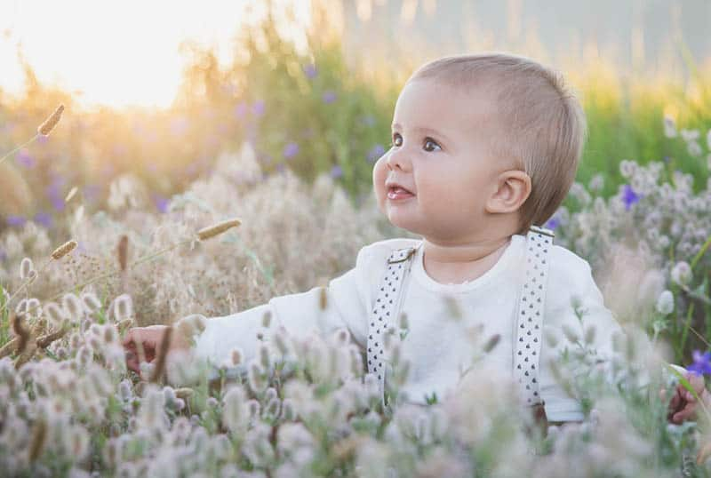 beautiful blond baby in a suit with suspenders sits in the grass