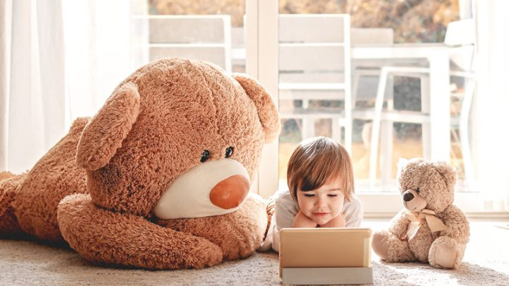 cute little boy watching cartoons on the floor with teddy bears