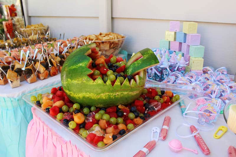 big watermelon with fruits and other food with decorations on the table