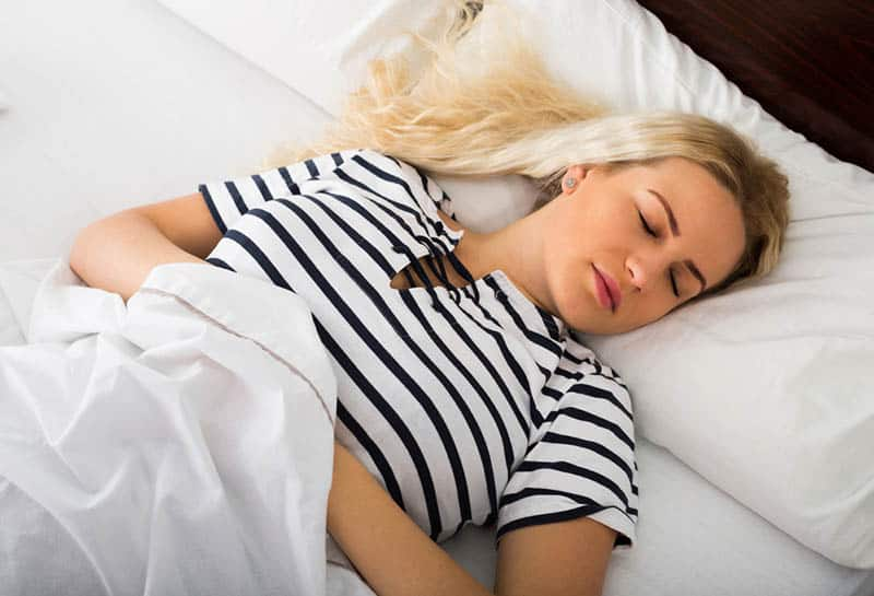 blond woman taking a nap in the bed covered with white sheet