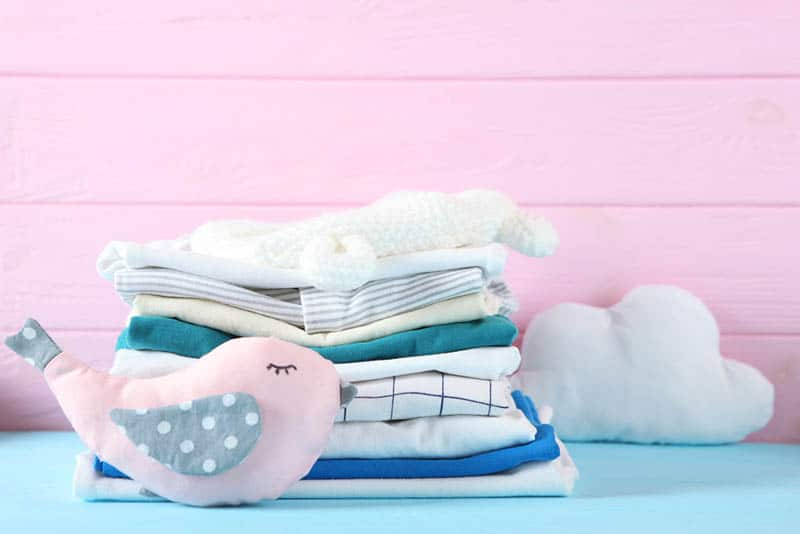 complex baby clothes with toys on the blue table