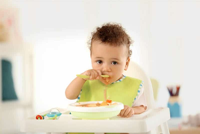 cute baby boy eating alone with spoon in high chair at home