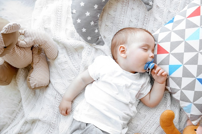 cute baby boy with pacifier sleeping on blanket with pillows and toys