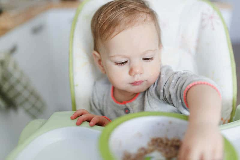cute baby girl sitting in the high chair and eating food with hands