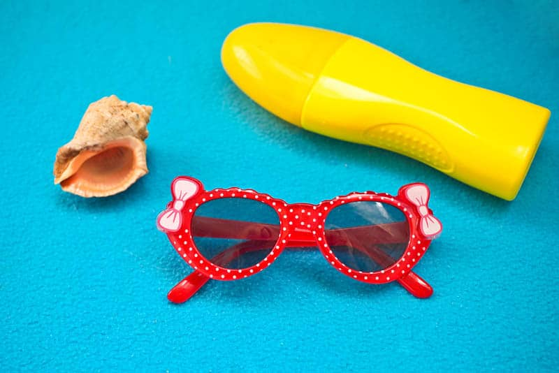 cute baby glasses with sunscreen and a shell on a blue towel