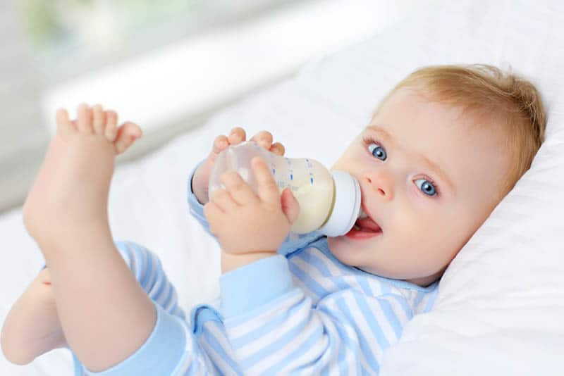 cute baby lying on bed and drinking milk bottle