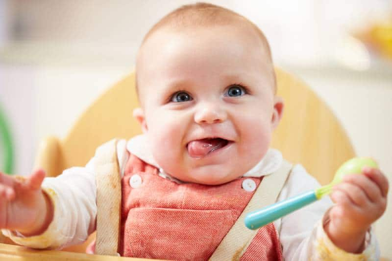 cute baby sitting in a high chair with spoon for eating