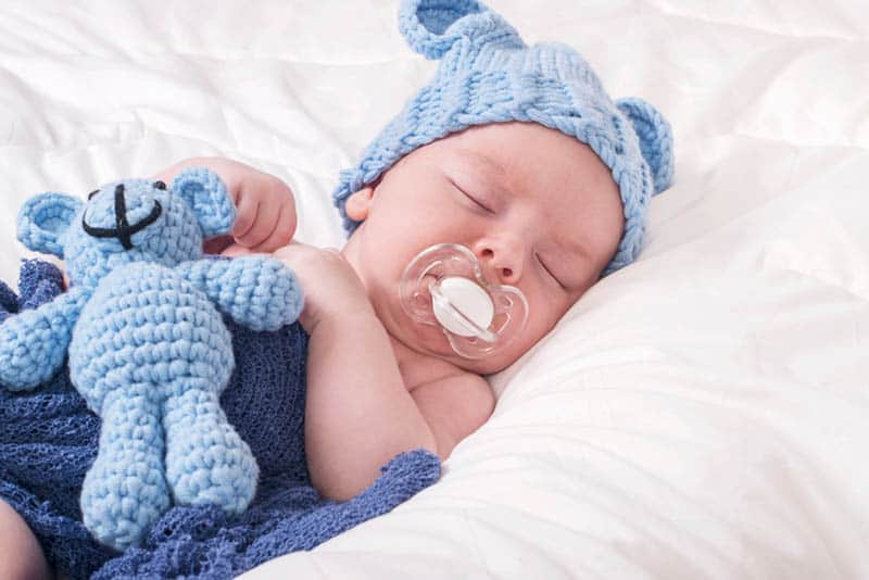 cute baby with winter hat and a pacifier sleeping in bed with his bunny toy