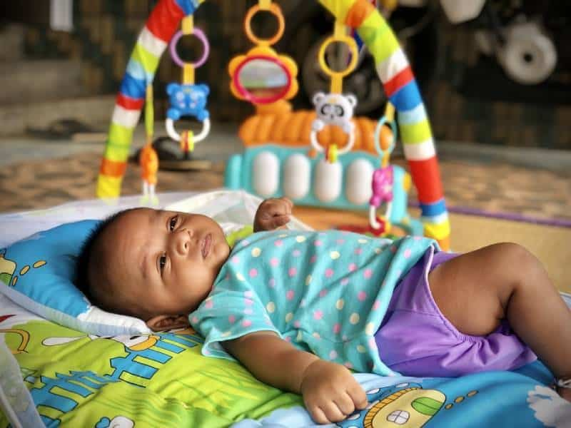 cute little baby lying on the playing mat in front of the baby gym