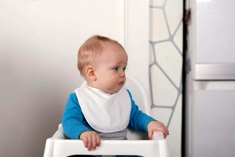 cute sad baby boy sitting in a high chair wearing bib and waiting for food