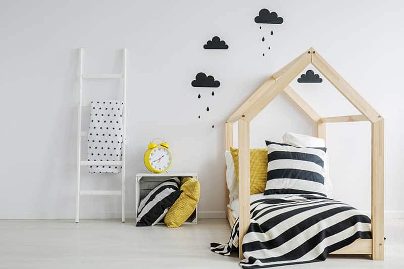 cute toddler bed with interesting wall with black clouds on it