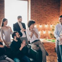 friends admiring a pregnant woman and her husband at a baby shower