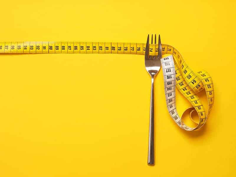 fork and measuring tape on a yellow background