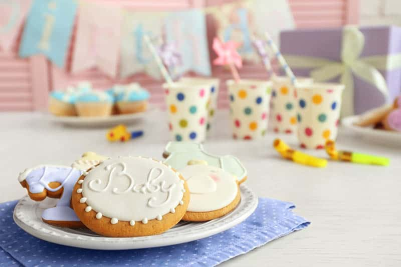 glazed cookies on the plate with glasses and decorations on the table for baby shower