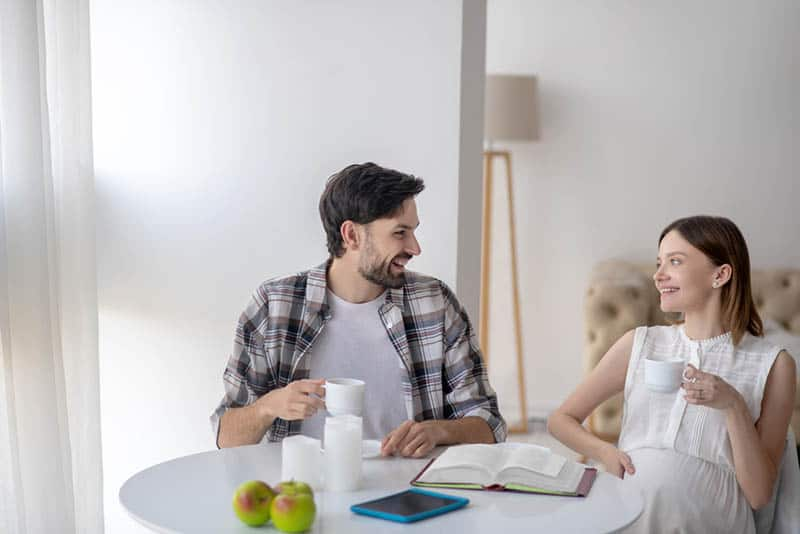 happy pregnant woman talking with her husband by the table at home