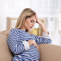 young pregnant woman on the couch holding for head